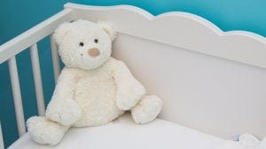 teddy in corner of baby cot